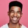 jeune homme souriant sur fond rose